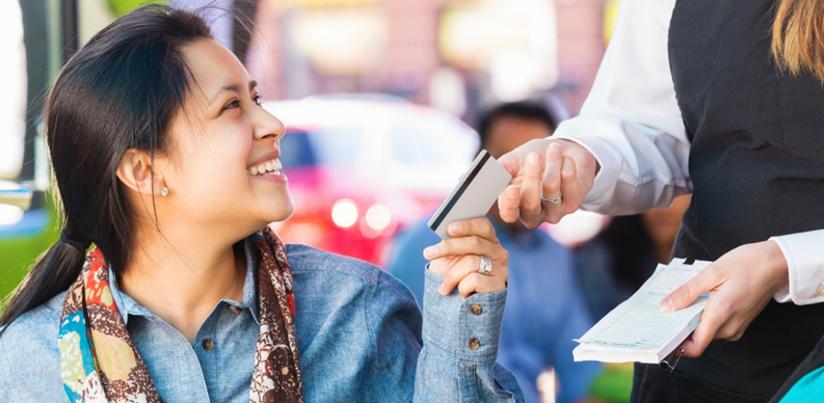 Hispanic woman paying at restuarant